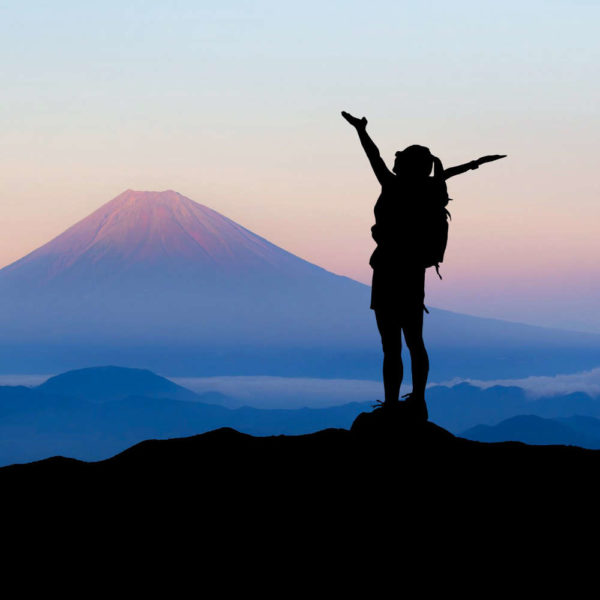 Frau ist auf Berggipfel angekommen